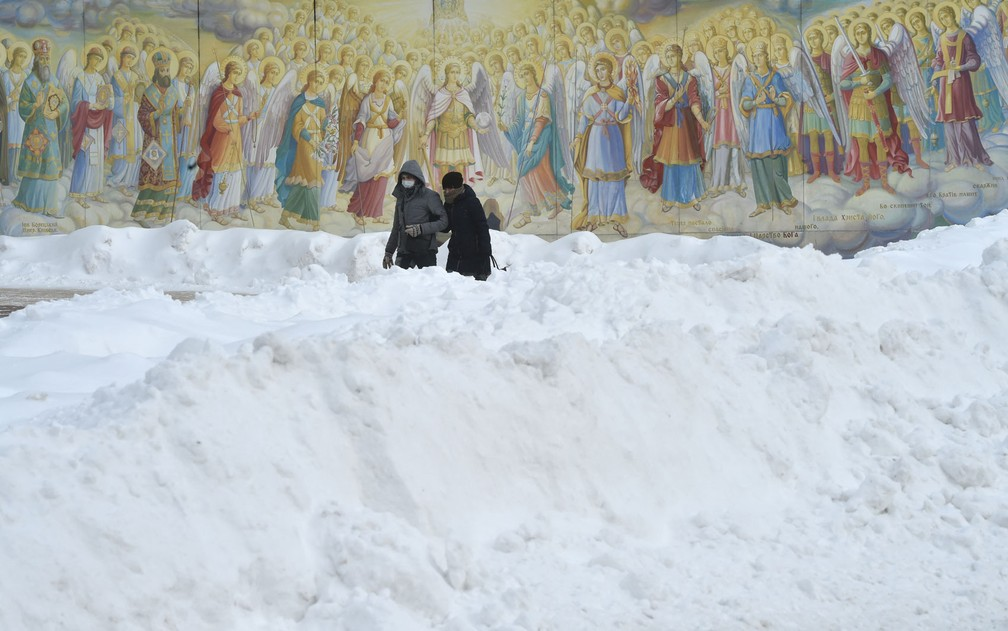 Casal caminha em meio a neve em Kiev, na Ucrânia, na sexta-feira (12) — Foto: Sergei Supinsky/AFP