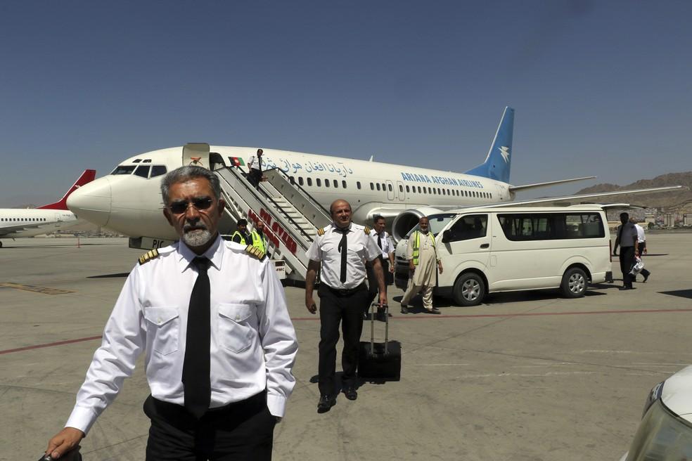 Pilotos da Ariana Afghan Airlines caminham na pista do Aeroporto Internacional Hamid Karzai, em Cabul, em 5 de setembro de 2021. Voos domésticos foram retomados no aeroporto internacional de Cabul, com a companhia aérea estatal Ariana Afghan Airlines voltando a operar voos para três províncias. — Foto: Wali Sabawoon/AP