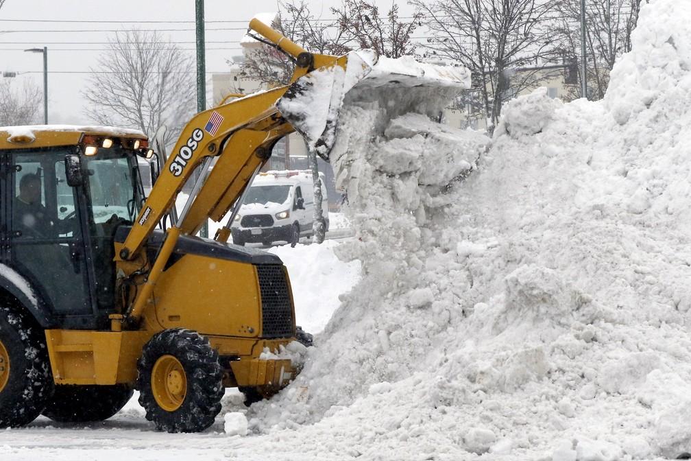 Homem retira grande quantidade de neve acumulada em estacionamento em Marlborough, nos EUA, nesta segunda-feira (2) — Foto: Bill Sikes/AP Photo