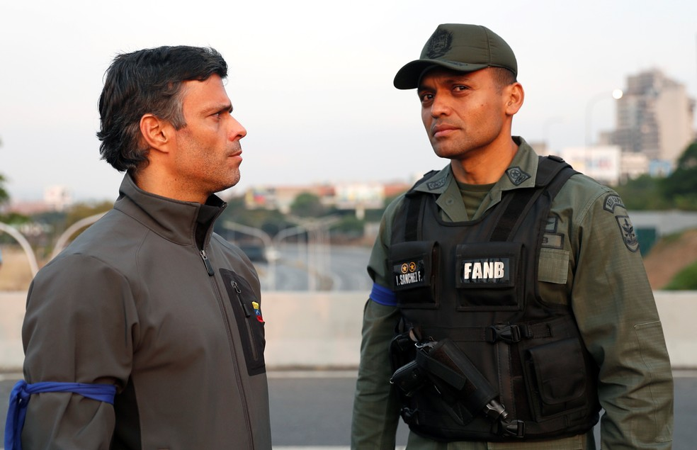 Leopoldo Lopez, que cumpria prisão domiciliar, ao lado de militar ao lado de base aérea em Caracas — Foto: Carlos Garcia Rawlins/Reuters