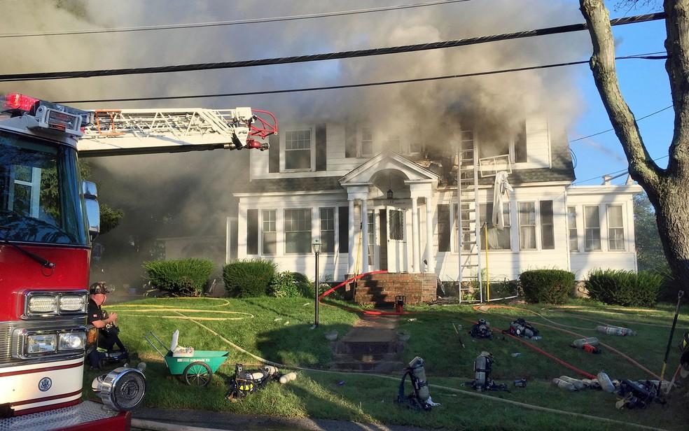Bombeiros combatem incêndio em uma casa na Herrick Road em North Andover, Massachusetts, na quinta-feira (13) — Foto: AP Photo/Mary Schwalm