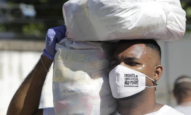 Voluntário da Frente de Mobilização da Maré carrega cestas básicas a serem distribuídas na comunidade, em maio