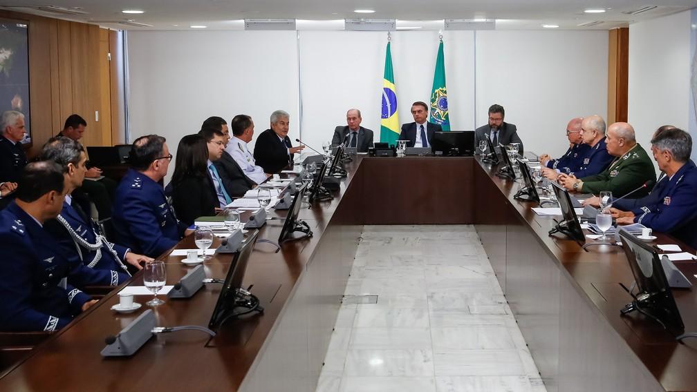 O presidente Jair Bolsonaro (ao fundo) durante reunião com ministros, no Palácio do Planalto, sobre o acordo entre Boeing e Embraer — Foto: Isac Nóbrega / PR