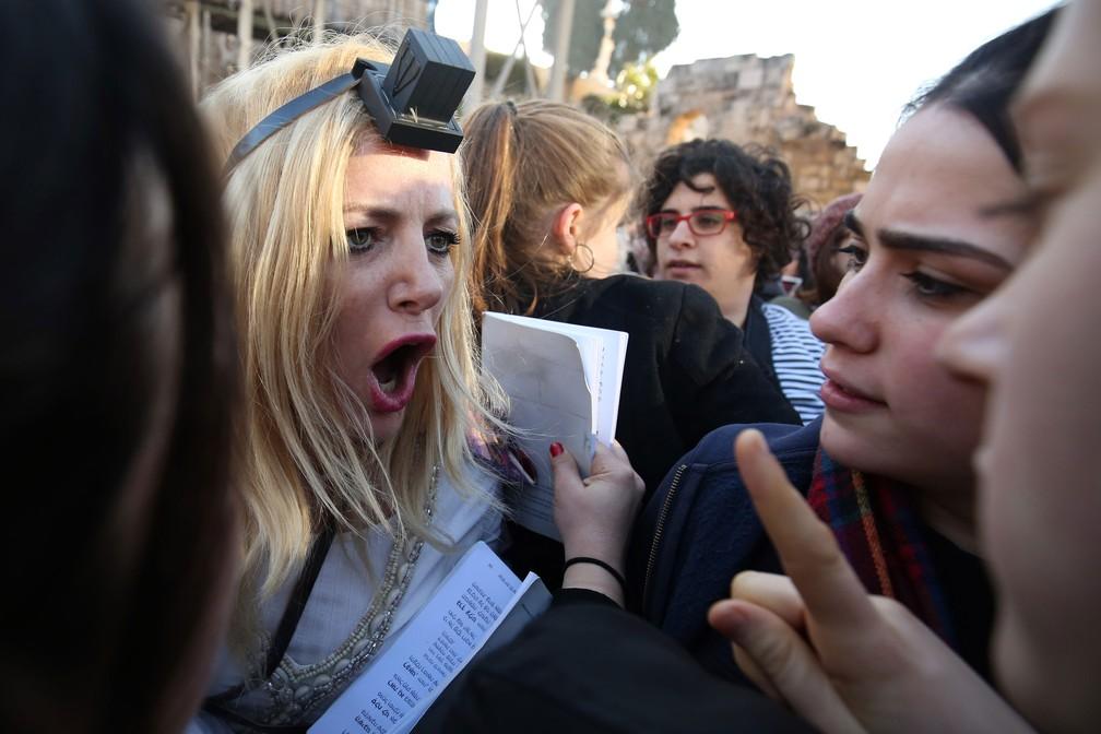 """Integrante do movimento religioso judeu progressista """"Mulheres do Muro"""" discute com meninas judias ultra-ortodoxas no Muro das Lamentações na Cidade Velha de Jerusalém, nesta sexta-feira (8)  — Foto: Gali Tibbon / AFP"""