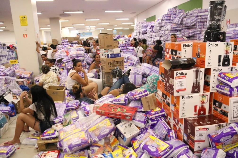 Clientes usam pacote de fraldas para esperar andamento das filas da Loja Americana, que fica na área central do Recife  — Foto: Marlon Costa/Pernambuco Press