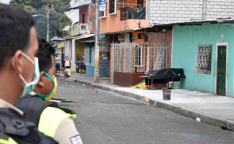 Policiais olham caixão com possível vítima da Covid-19 em frente a uma casa no subúrbio de Guayaquil, no Equador, em 3 de abril de 2020  — Foto: Edison Choco/AP