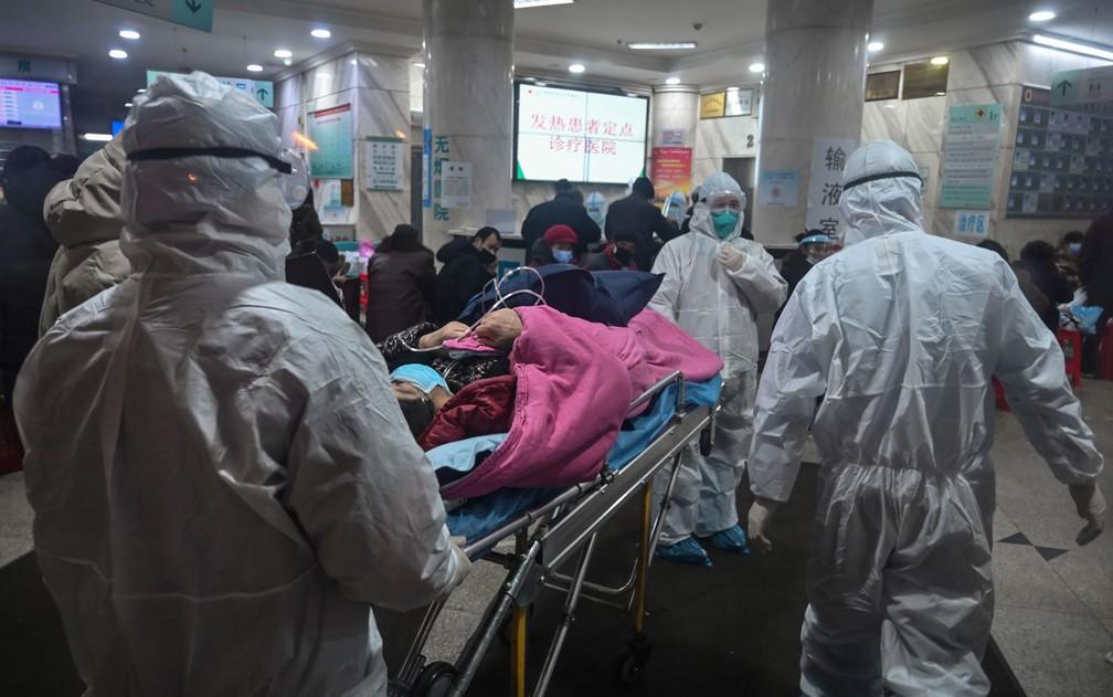 Equipe médica transporta paciente em hospital da Cruz Vemelha, em Wuhan, na China — Foto: Hector Retamal/AFP