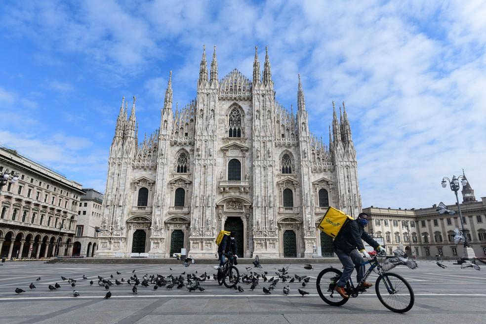 Ciclistas que trabalham com entrega de alimentos passam pela Piazza Duomo em Milão, na Itália, que estava deserta na terça-feira (31) — Foto: Piero Cruciatti / AFP