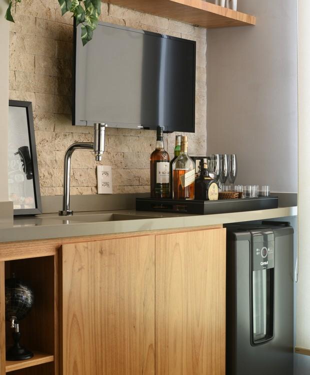A bancada de apoio da varanda tem tudo necessário para receber as visitas, incluindo um bar na bancada e uma adega climatizada na parte inferior (Foto: Laura Sá/Divulgação)