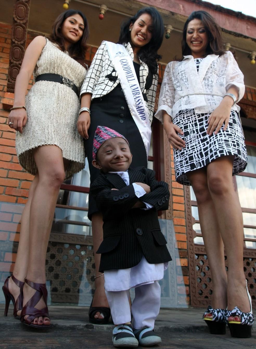 Khagendra Thapa Magar é fotografado com miss Nepal de 2010, Sadichha Shrestha (no centro), e as duas vices da miss em Katmandu no Nepal, em 24 de setembro de 2014  — Foto: Prakash Mathema / AFP