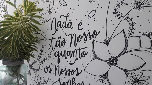 """A paisagista Rayra explica a escolha da espécie: """"A frase da parede vem acompanhada de desenhos de plantas em preto e branco. Colocamos a pleomere verde, por ter uma tonalidade que é uma mistura de verde, amarelo e branco. Dessa forma, levamos de maneira sutil mais uma plantinha a um cantinho da casa"""" (Foto: Rayra Lira Araújo / Divulgação)"""