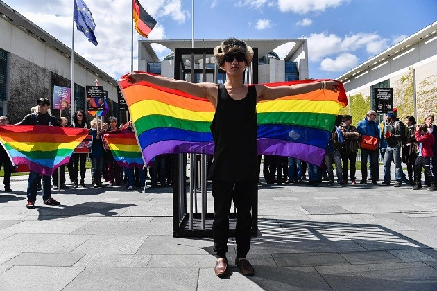 Ativista exibe bandeira em Berlim durante protesto que pede que o presidente russo Vladimir Putin acabe com a perseguição de gays na Chechênia. Foto: John Macdougall / AFP