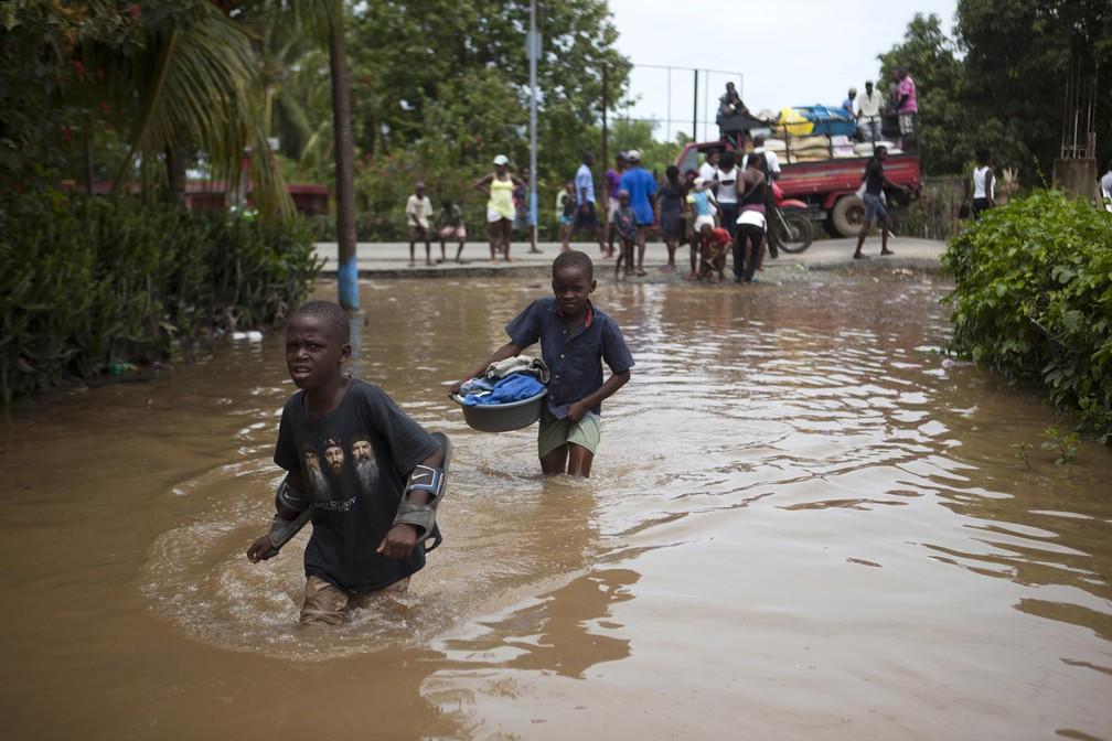 Meninos atravessam as águas das inundações causadas por fortes chuvas provocadas pelo furacão Irma, em Fort-Liberte, no Haiti (Foto: Dieu Nalio Chery/AP)