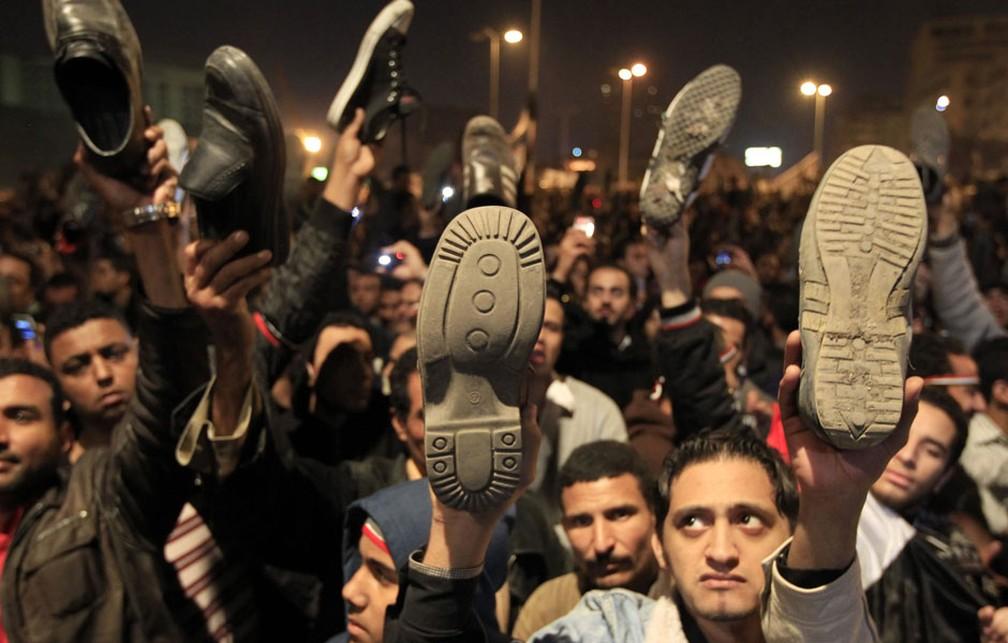 Manifestantes na praça Tahrir mostram sapatos durante fala do presidente Hosni Mubarak — Foto: Goran Tomasevic / Reuters