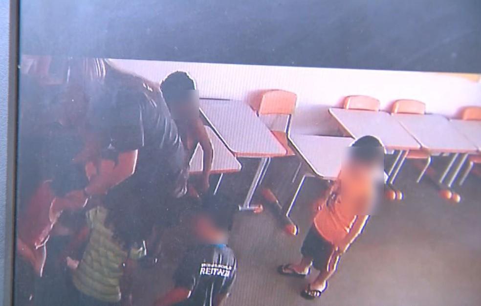 No canto esquerdo, a estagiária segura a criança, enquanto a professora tentar puxar o saco e fechá-lo em Restinga, SP (Foto: Câmeras de segurança)
