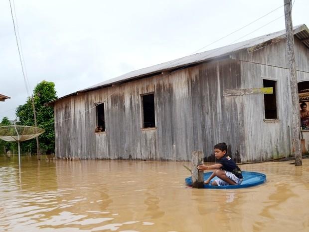 Menino usa tampa de caixa d'água durante enchente (Foto: Vanísia Nery/G1)