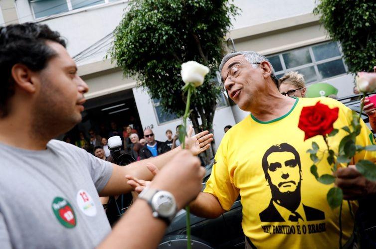 Apoiador de Haddad entrega rosa a um eleitor de Bolsonaro em São Paulo  (Foto: Nacho Doce/Reuters /Direitos Reservados)