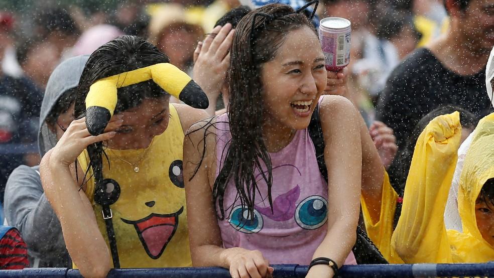 Fãs com camisetas do Pikachu e Jigglypuff tomam banho de água durante evento de 'Pokémon Go' no Japão (Foto: REUTERS/Kim Kyung-Hoon)