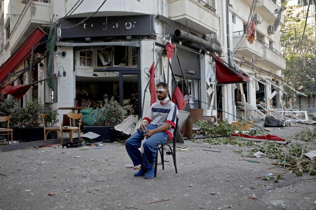 5 de agosto - Homem ferido é visto sentado ao lado de restaurante no parcialmente destruído bairro de Mar Mikhael, em Beirute — Foto: Patrick Baz/AFP