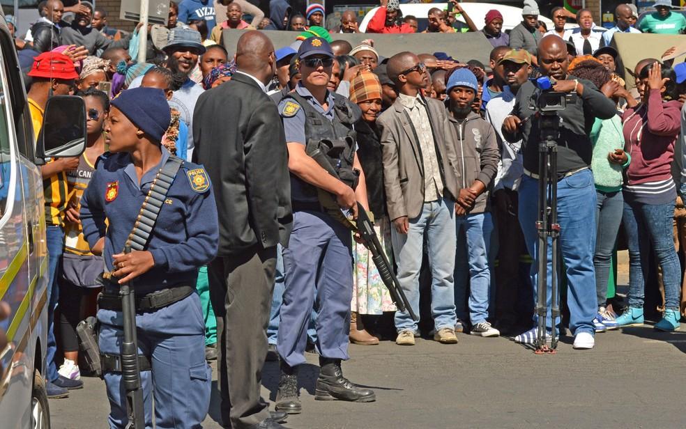 Policiais armados são vistos do lado de fora do tribunal de Estcourt, na África do Sul, na segunda-feira (21), durante audiência com acusados de homicídio e canibalismo (Foto: AP Photo)