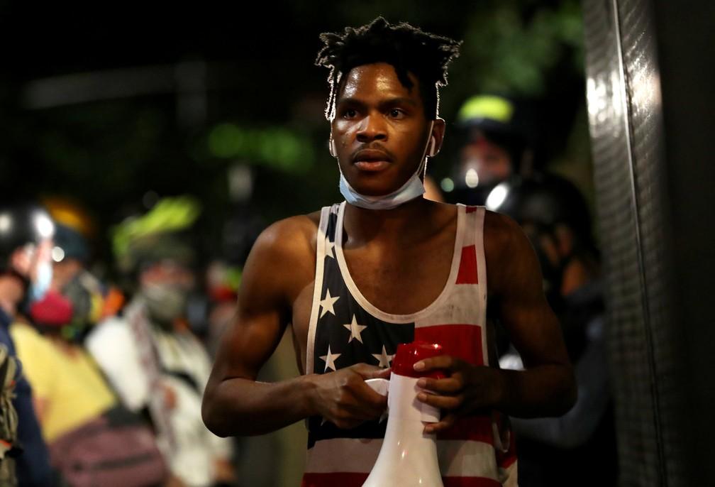 Manifestante segura megafone com o qual frases contra a desigualdade racial e a violência policial nos EUA, neste domingo, em Portland — Foto: Caitlin Ochs/Reuters
