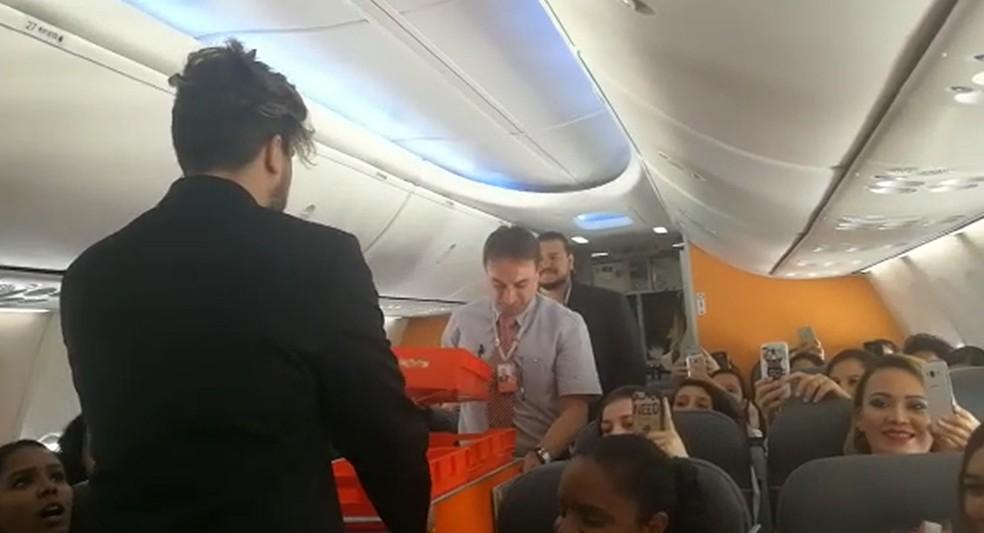 Luan Santana distribui sanduíches aos fãs durante voo para lançar clipe (Foto: G1)