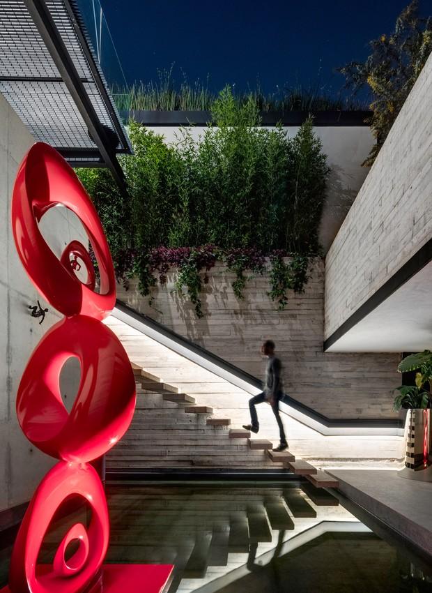 Uma escultura vermelha flutua sobre o espelho d'água e a escada de concreto é iluminada por um feixe de luz que acompanha a altura dos degraus  (Foto:  Rafael Gamo/ Reprodução)