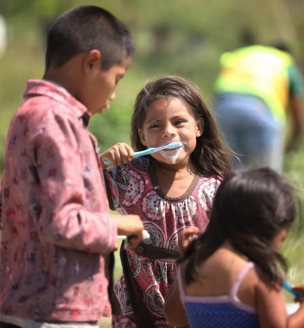 Crianças escovam os dentes durante a marcha migratória (Foto: Héctor Alfaro)