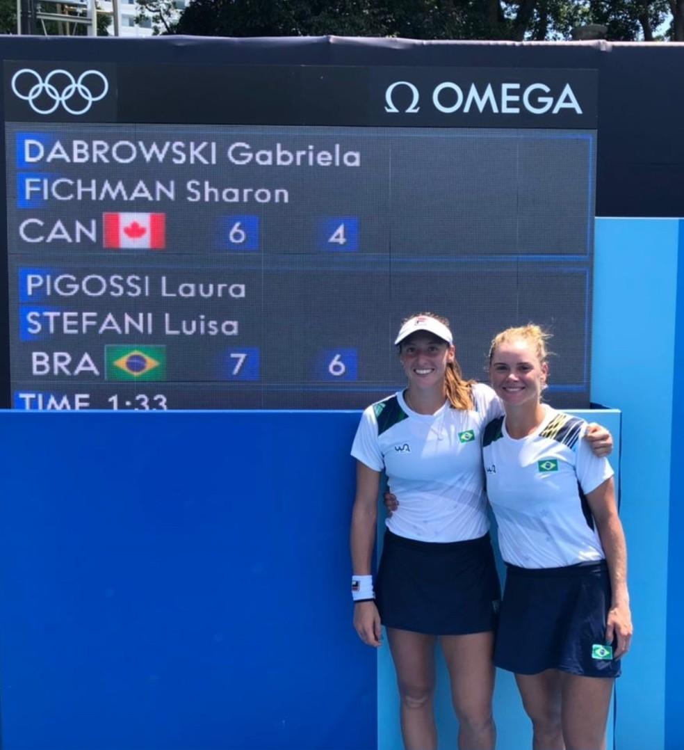 Olimpíadas 2020: Luisa Stefani e Laura Pigossi posam com placar da vitória na estreia das duplas femininas do tênis — Foto: Divulgação / CBT