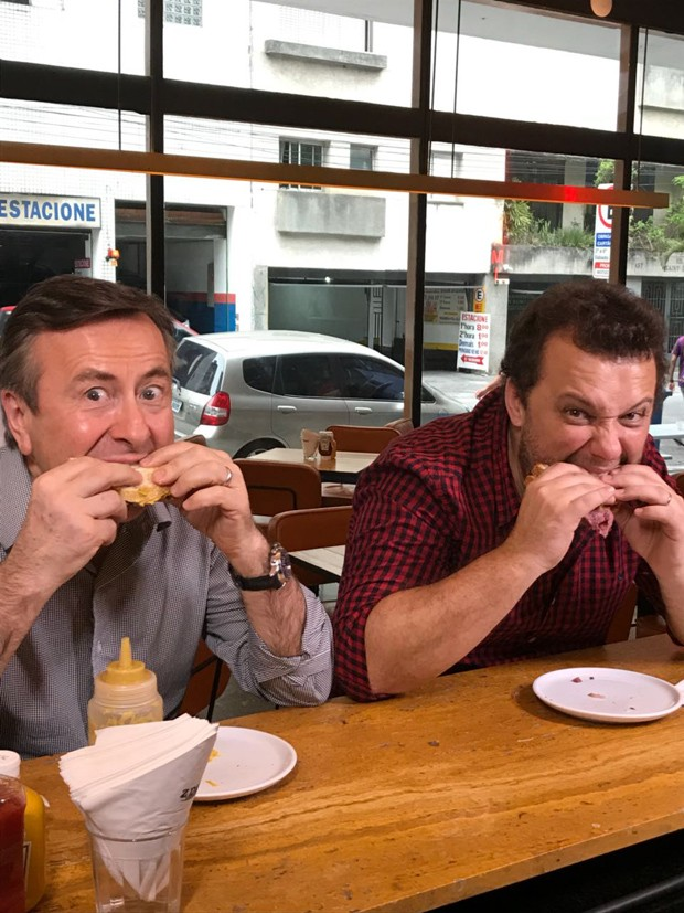 Os chefs Daniel Boulud e Thomas Troigros abocanhando um cheeseburger no Z Deli, em São Paulo (Foto: Mariana Fonseca)