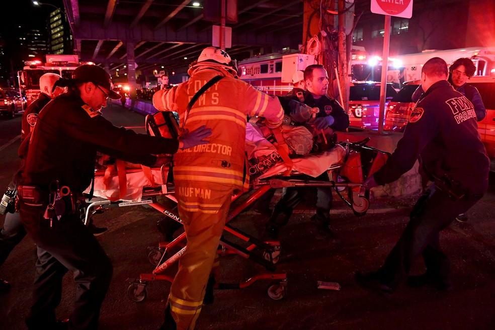 Paramédicos resgatam vítima de queda de helicóptero no East River, em Nova York, neste domingo (11) (Foto: REUTERS/Darren Ornitz)