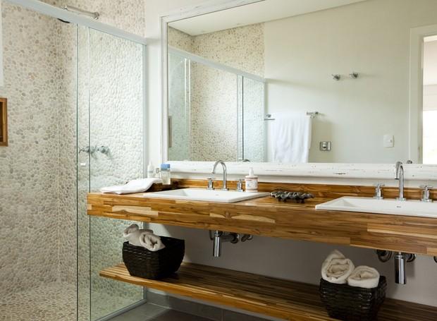 Para levar a natureza para dentro do banheiro de 7 m² , a arquiteta Ana Karina Abud projetou o boxe com revestimento de seixos telados na cor areia. As duas pias ficam sobre a bancada de madeira teca (Foto: Edu Castello / Casa e Jardim)