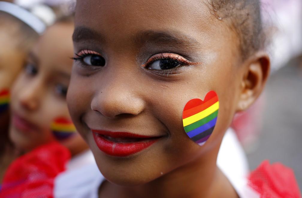 Uma criança com um adesivo em forma de coração em sua bochecha, sorri enquanto espera para dançar em um desfile que marca o Dia Internacional contra Homofobia, Transfobia e Bifobia, em Pinar Del Rio, Cuba (Foto: Desmond Boylan/AP)