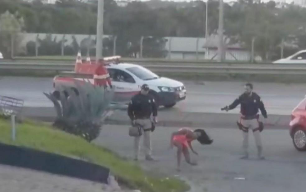 Momento em que travesti, depois de colocar vestido, é atingida por arma de choque de PRF — Foto: Reprodução/TV Anhanguera