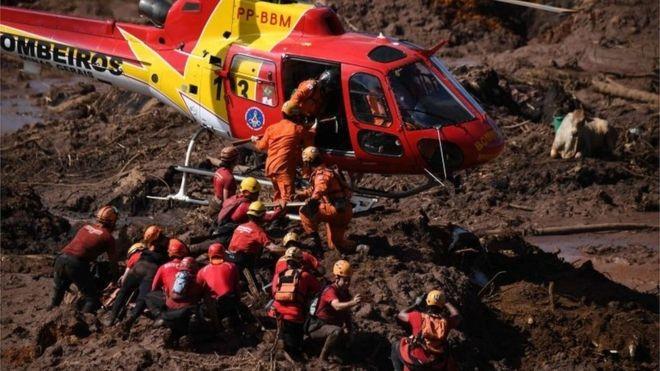 Bombeiros resgatam vítimas do desastre em Brumadinho, onde barragem da mineradora Vale rompeu na sexta (Foto: AFP via BBC)