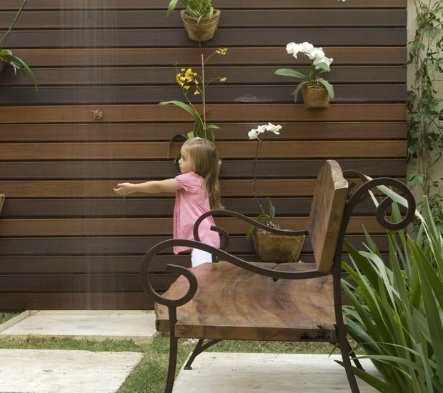 A pequena Sophia sempre deixa a sua brinquedoteca para curtir o jardim. Ao fundo, as orquídeas dão cor ao painel vertical de madeira, que recebeu um chuveirão para refrescar as crianças nos dias de calor. Projeto da paisagista Irene Cisneros (Foto: Evelyn Müller e Tatiana Villa/Casa e Jardim)