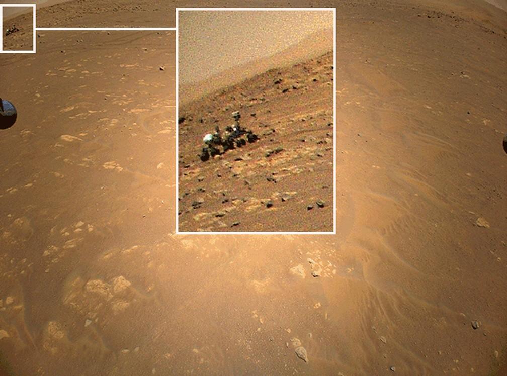 A Ingenuity fotografou o Perseverance durante seu terceiro vôo. Na época, o mini-helicóptero estava a cerca de 85 m do rover e voando lateralmente a uma altitude de 5 m. Um dos pés do Ingenuity também é visível na borda da imagem, logo abaixo do veículo espacial. — Foto: Nasa