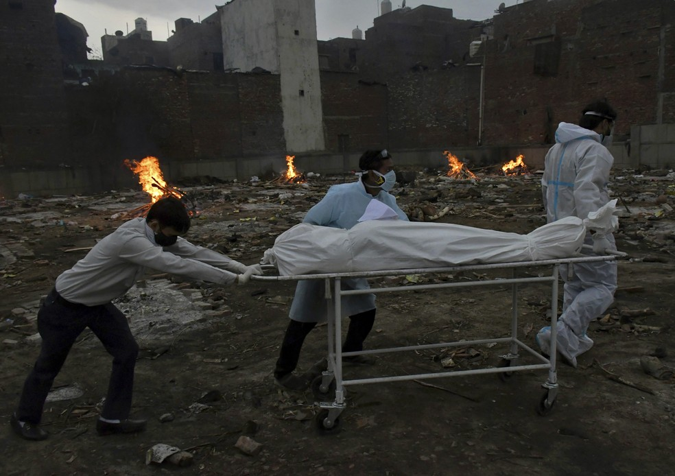 Trabalhadores transportam corpo de vítima da Covid-19 para cremação em local convertido em crematório em Nova Délhi, capital da Índia, em 6 de maio de 2021 — Foto: Ishant Chauhan/AP