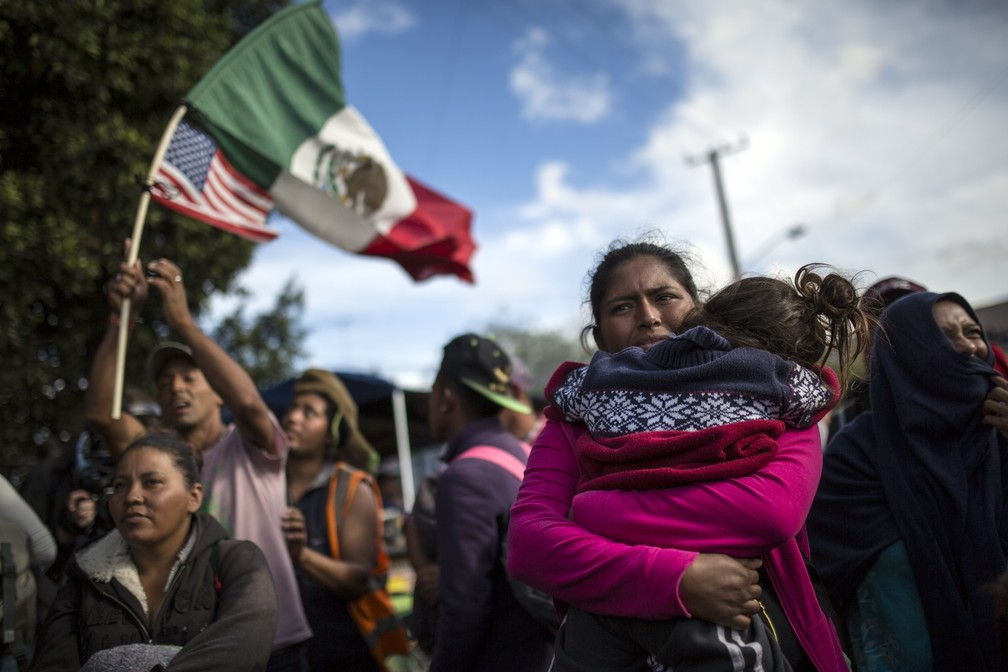 Família de migrantes centro-americanos protestam nesta quinta-feira (22) em El Chaparral, na fronteira com os EUA, onde pretendem entrar para pedir refúgio — Foto: Rodrigo Abd/AP Photo