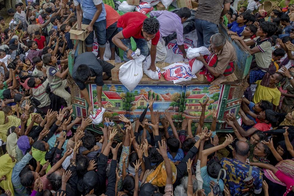 Refugiados rohingya, que recentemente atravessaram a fronteira entre Mianmar e Bangladesh, esticam os braços para pegar alimentos distribuídos por agências humanitárias, perto do campo de refugiados de Balukhali, Bangladesh (Foto: Dar Yasin/AP)