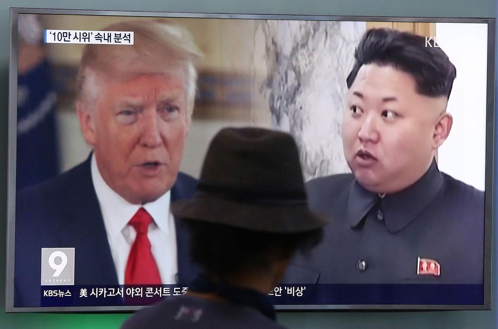 Homem observa imagem do presidente americano, Donald Trump, e do líder norte-coreano, Kim Jong-un, em Seul, na Coreia do Sul  (Foto: Ahn Young-joon/ AP)