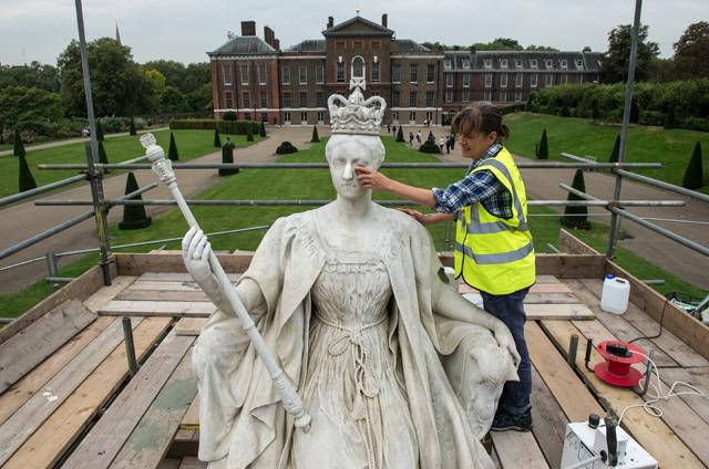 Funcionária limpa a estátua da rainha Victoria, construída em 1893; Ao fundo, o Palácio de Kensington, onde moram Príncipe William e família e onde também morará o príncipe Harry com a mulher, Meghan (Foto: Getty Images)