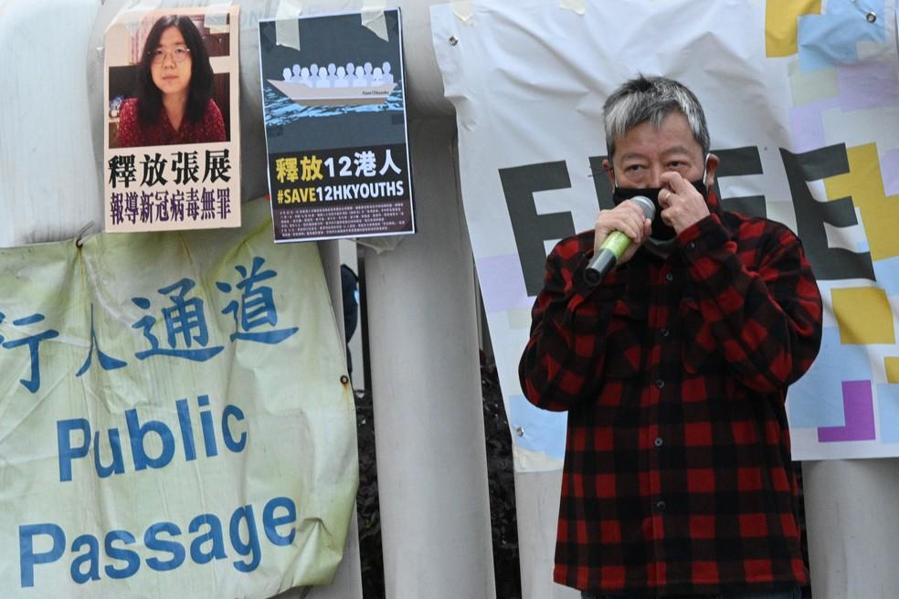 O ativista pela democracia Lee Cheuk-Yan protesta pedindo liberdade à Zhang Zhan (em foto no pôster à esquerda), condenada a quatro anos de prisão por cobrir a pandemia de Covid em Wuhan. — Foto: Peter PARKS / AFP