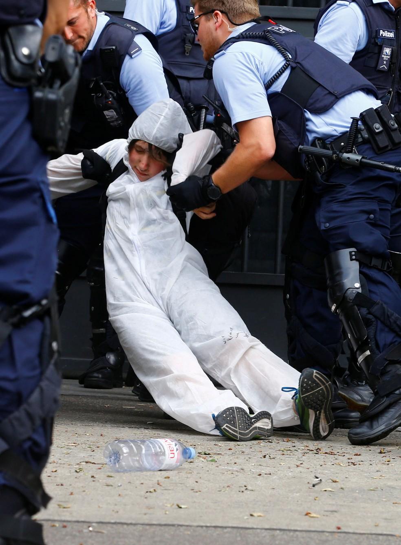 Policiais prendem ativista ambiental que bloqueava a entrada do banco Credit Suisse, em Zurique, nesta segunda-feira (8). — Foto: Arnd Wiegmann/Reuters