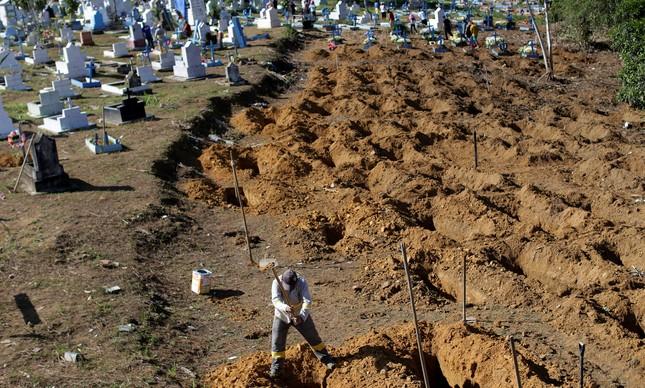 Coveiro prepara sepulturas para vítimas de chacina em presídio no norte do país