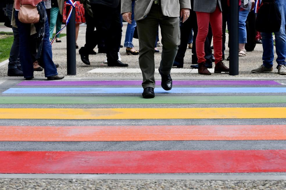 Pessoas caminham em um cruzamento de pedestres pintado nas cores da bandeira do arco-íris, um símbolo do movimento dos direitos dos homossexuais, para marcar o Dia Internacional contra Homofobia, Transfobia e Bifobia, em Perigueux, na França — Foto: Georges Gobet/AFP