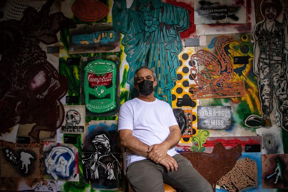 Ozi diante de um paredão coberto de várias de suas matrizes de estêncil, parte da exposição retrospectiva de 35 anos de carreira — Foto: Fábio Tito/G1