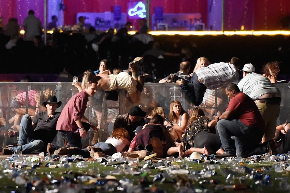 Pessoas pulam uma grade para se proteger dos disparos feitos por um atirador durante um festival de música country em Las Vegas, nos EUA (Foto: David Becker/Getty Images/AFP)