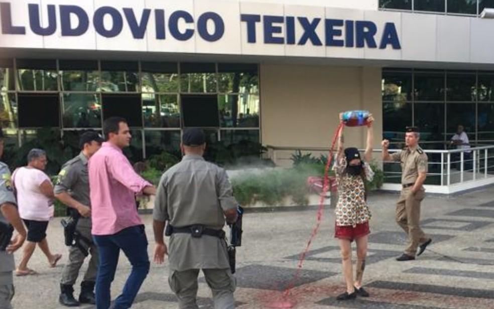 Estudante joga líquido vermelho em frente à sede do Governo de Goiás — Foto: Rodrigo Gonçalves/G1