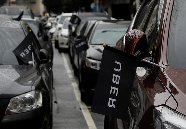 Carros do Uber com bandeiras da empresa (Foto: Tyrone Siu/Reuters)